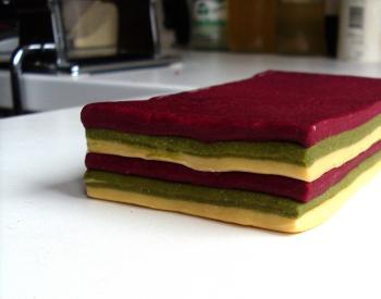 So mache ich gestreifte Nudeln: Gleich große Lagen farbigen Nudelteigs werden leicht angefeuchtet gestapelt....