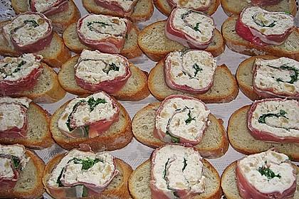 Parmaschinkenröllchen mit Frischkäse und Basilikum auf Röstbrotscheiben