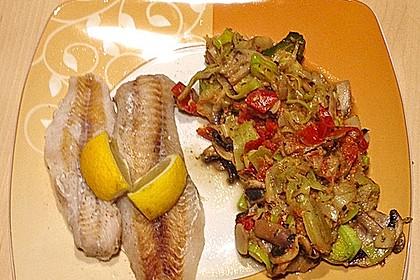 Fisch mit einer Gemüsepfanne und Zitrone