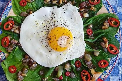 Senfkohl mit geröstetem Knoblauch, Zwiebeln und Spiegelei. Eine beliebte Vorspeise in Bali, Indonesien.
