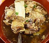 Klare und kräftige Rindfleischsuppe mit fleischigen Knochen (Bild)