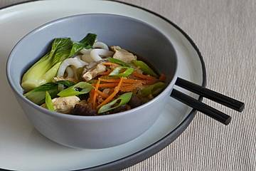 Udon-Nudel-Suppe mit Hähnchenfleisch, Shiitake, Pak Choi und Möhren