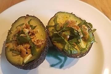Avocadohälfte mit Basilikum, Walnüssen und Limette