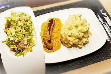 Thüringer Rostbratwurst auf Curryrahmsoße mit Kartoffelstampf und Romana-Tomaten-Salat