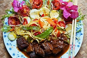 Exotisches Ziegengulasch mit bunten Nudeln und Salat