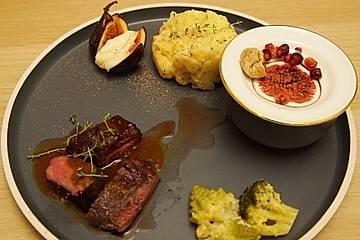 Rehrücken unter Himbeer-Pfeffer mit Pastinaken-Thymian-Stampf, geschmolzenem winterlichem Gemüse und Rotkohlsalat