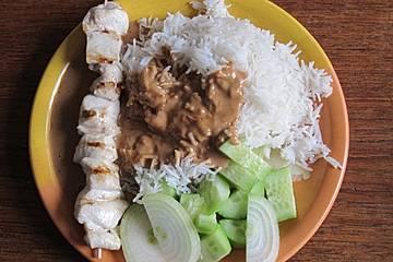 Saté Hühnerspieß in Erdnussbuttersauce mit Reis, Zwiebeln und Gurke