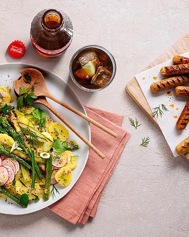 Moderner Kartoffelsalat mit grünem Spargel, Bohnen und vegetarischen Rostbratwürstchen