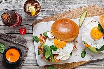 Brekkie Buns mit Avocado, Babyspinat, Bacon, Büffelmozzarella und Spiegelei