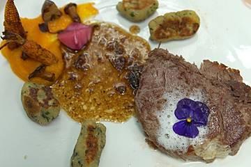Rinderfilet, getoppt mit Parmesanschaum, dazu Spinatgnocchi, Rinderjus und Variationen von Herbstgemüse